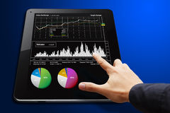 Smart hand touch on Tablet with graph report Stock Image