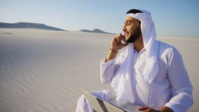 Handsome Arabian UAE Sheikh guy businesswoman calling business p. Smart handsome emirate Arabian UAE Sheikh businessman prints on computer keyboard and answers royalty free stock images