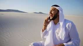 Handsome Arabian UAE Sheikh guy businesswoman calling business p. Smart handsome emirate Arabian UAE Sheikh businessman prints on computer keyboard and answers royalty free stock photography