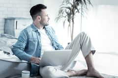 Smart handsome man turning his head. Thoughtful look. Smart nice handsome man holding his laptop and turning his head aside while looking for new ideas Royalty Free Stock Photo