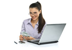 Smart and happy brunette!. Portrait of happy greedy for money woman with a fan of American dollar using laptop Royalty Free Stock Photo