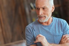 Positive aged man folding his hands stock images