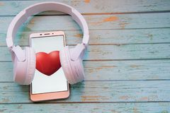 Smart heart beats. Smartphone with earphones on a wooden blue background. Mobilephone with a red heart. White earphones on a brown wooden texture Stock Images