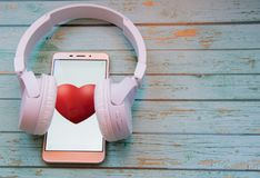 Smart heart beats. Smartphone with earphones on a wooden blue background. Mobilephone with a red heart. White earphones on a brown wooden texture Stock Photo