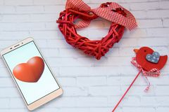 Smart heart beats. Smartphone with red hearts and red bird on a white background. St Valentine`s theme. Mobilephone with a red heart. Red hearts and a bird Royalty Free Stock Photography