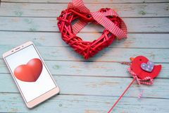 Smart heart beats. Smartphone with red hearts and red bird on a wooden blue background. St Valentine`s theme stock photos