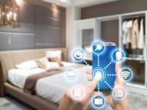 Smart hem- automation app på mobil med hemmiljön i backgr arkivbild