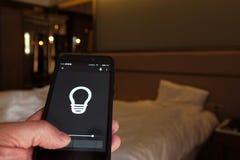 Smart hem: man att kontrollera ljus med app på hans telefon elektriskt begrepp royaltyfria bilder