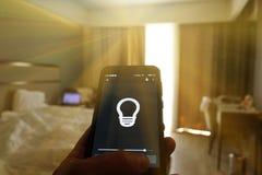 Smart hem: man att kontrollera ljus med app på hans telefon elektriskt begrepp royaltyfri fotografi