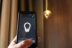Smart hem: man att kontrollera ljus med app på hans telefon elektriskt begrepp arkivbild