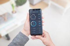 Smart hemkontroll app för mobila enheter i kvinnahand Vardagsruminre i bakgrund royaltyfri bild
