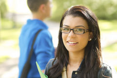 Smart hispanic female student. A close up of a beautiful female student wearing glasses outdoors Royalty Free Stock Photo