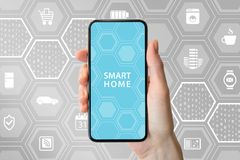 Smart home automation concept with hand holding modern bezel-free smartphone in front of neutral background with icons of applianc. Es Royalty Free Stock Images