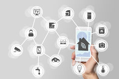Smart home automation concept illustrated by modern smart phone to monitor smart objects. Stock Photo