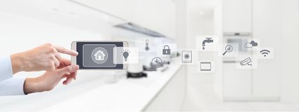 Smart home automation control concept hand touch cell phone screen with grey symbols icons on kitchen background web banner and c. Opy space template royalty free stock photos