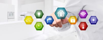 Smart home automation control hand touch screen with colored symbols on white kitchen background web banner and copy space. Template royalty free stock photos