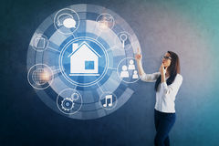 Smart home concept. Attractive young woman pointing at circular futuristic interface of smart home automation assistant on concrete background. 3D Rendering Royalty Free Stock Images