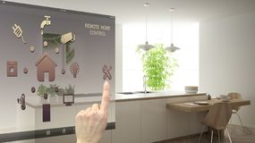 Smart home control concept, hand controlling digital interface from mobile app. Blurred background showing modern white and wooden. Modern kitchen, architecture stock photography