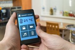 Smart home control concept. Man is adjusting temperature with smartphone Royalty Free Stock Photography