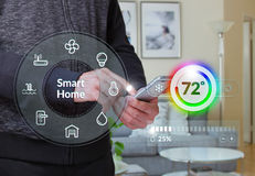 Smart Home Control System. Smart home control dashboard with male using smartphone at home in the background Stock Images