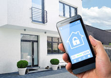 Smart Home Device - Home Control. Smart house, home automation, device with app icons. Man uses his smartphone with smarthome security app to unlock the door of royalty free stock image