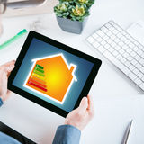 Smart home online energy efficiency chart. Smart home online energy efficiency rating chart displayed on the screen of a tablet held in the hands of a stock images