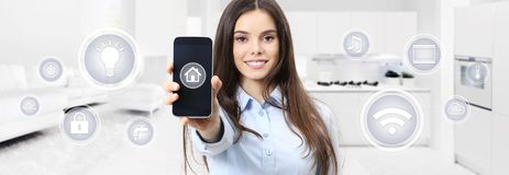 Smart home smiling woman showing cell phone screen with symbols Stock Image