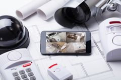 Smart Home System On Mobilephone With Security Equipment. High Angle View Of Smart Home System On Mobilephone With Security Equipment And Blueprint stock photo