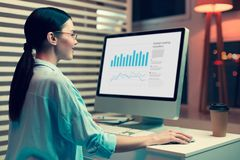 Upbeat female analyst working on a bar graph. Smart ideas. Pleasant upbeat female analyst sitting at the table in her office and working on a bar graph stock photo