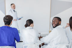 Smart interns listening to lecturer with interest. I like studying. Happy african future doctor is sitting on lecture and smiling. He is looking at camera with Royalty Free Stock Image