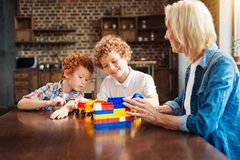 Smart joyful children spending free time with granny. There is no place like home. Selective focus on smiling curly haired brothers playing with a building Stock Images