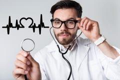 Smart kardiolog som rymmer en stetoskop, medan undersöka hans patient arkivfoton