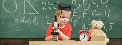 Smart kid concept. Child on happy face holds microscope. First former interested in studying, learning, education. Kid. Boy in academic cap work with microscope royalty free stock photo