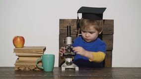 Smart kid concept. Child with a serious facial expression holds microscope. First former interested in studying. Learning, education. Kid boy in academic cap stock video footage