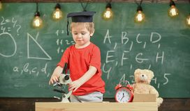 Smart kid concept. First former interested in studying, learning, education. Child on busy face near microscope. Kid boy. In academic cap work with microscope stock photography
