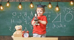 Smart kid concept. First former interested in studying, learning, education. Kid boy in academic cap work with. Microscope in classroom, chalkboard on royalty free stock image