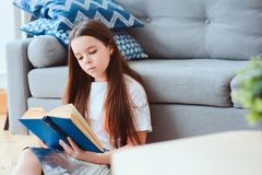 Smart kid girl reading interesting book. At home, sitting with couch on background. Learning and education concept stock photography