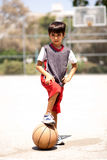 Smart kid holding basketball under his leg Royalty Free Stock Image