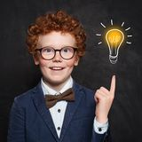 Smart kid with lightbulb. Brainstorming and idea concept. Little cute student boy on chalkboard background.  royalty free stock photo