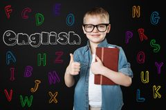 Smart kid putting his thumb up and feeling happy to learn English. Learning English. Positive enthusiastic little boy looking happy and putting his thumb up royalty free stock image
