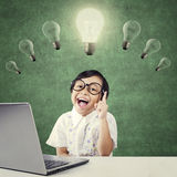 Smart kid sitting under lamp with laptop Royalty Free Stock Photography