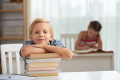 Smart kid. Smiling smart kid leaning on stack of books and looking at camera royalty free stock photography