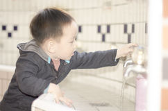 Smart kid washing hands with faucet Royalty Free Stock Photos