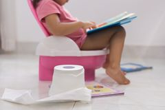 Toddler potty training. reading books on the toilet. Smart kids. Learning how to read. Toilet training. Child with toilet paper, potty, and books royalty free stock photography