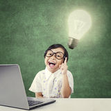 Smart kindergarten student with lamp and laptop Stock Photography