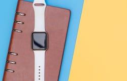 Smart klocka på anteckningsboken för att organisera med blå guling arkivfoto