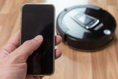 Smart kontroll för robotvakuumlokalvård med den smarta telefonen royaltyfria bilder
