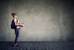 Smart kvinna, bärande exponeringsglas som rymmer högen av böcker royaltyfri foto