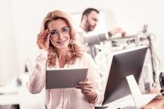 Smart kvinna i exponeringsglas som rymmer en minnestavla arkivfoton