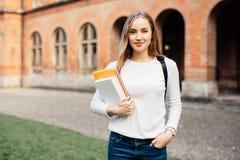 Smart kvinnlig högskolestudent med påsen och böcker på universitetsområde utomhus royaltyfri bild